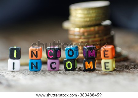Close-up of colourful alphabet block with word INCOME. With pile of coins in the background. - stock photo