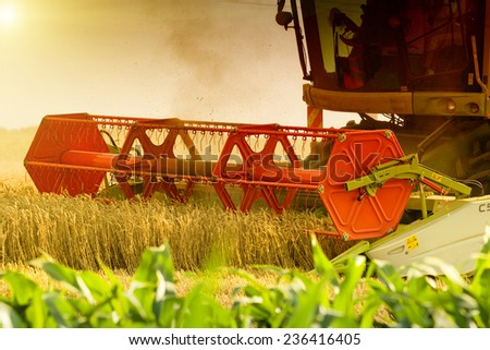 Close up of combine harvester working in wheat field - stock photo