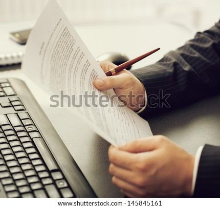 Close-up of company director's hands holding business document at the computer desk. Young financial specialist working over calculation papers.  - stock photo