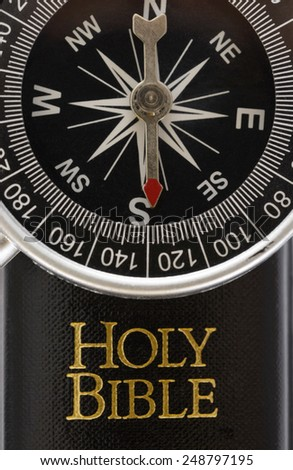 Close-up Of Compass Lying On Holy Bible - stock photo