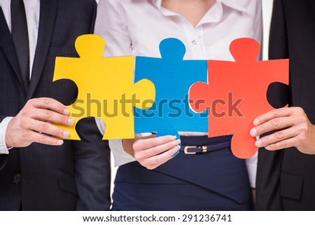 Close-up of confident business people wanting to put pieces of puzzle together. Team work. - stock photo