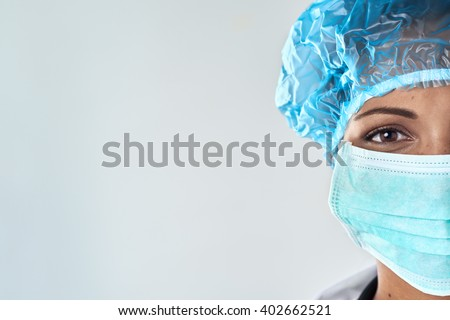 Close up of confident female surgeon in mask getting ready for medical procedure surgery