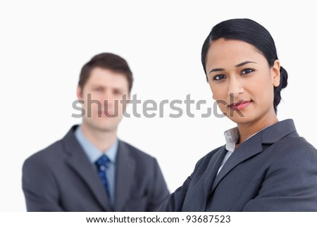 Close up of confident saleswoman with co-worker behind her against a white background - stock photo