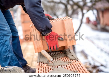 close-up of construction worker, bricklayer building new house with brick walls - stock photo