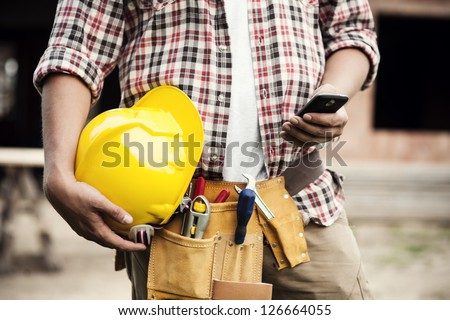 Close-up of construction worker sending text on mobile phone - stock photo