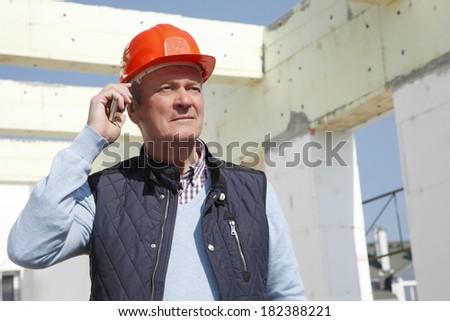 Close-up of construction worker standing and using his mobile in front of construction site. - stock photo