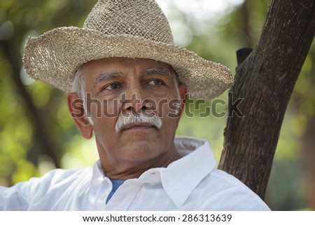 Close-up of contemplative senior man at park looking away in deep thought