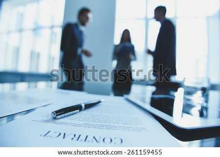 Close-up of contract with business people in the background - stock photo