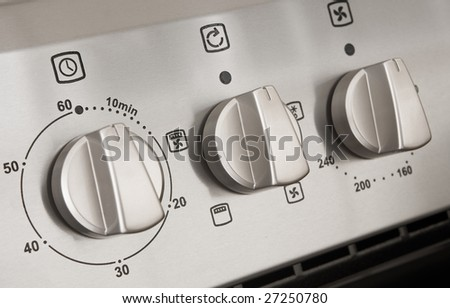 close up of controls from a modern stainless steel oven