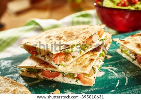 Close up of cooked chicken quesadillas on green cutting board with bowl of salsa and napkins in background - stock photo