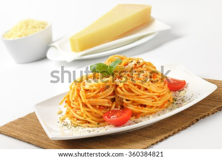close up of cooked spaghetti with red pesto and grated parmesan cheese on white plate and brown place mat - stock photo