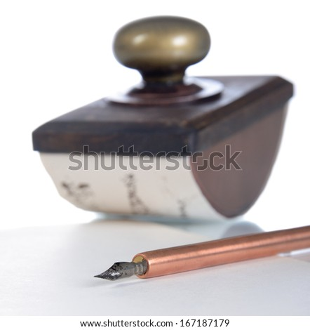 Close-up of copper ink pen and paperweight a on a white background. Low depth of field. - stock photo