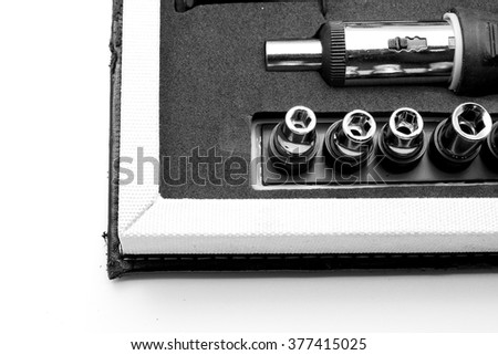 Close up of corner of tool box with screwdriver and adjustable torque. Isolated on white. Space for texts. - stock photo