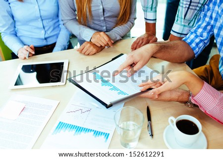 Close-up of corporate business people working at the table analyzing graph - stock photo