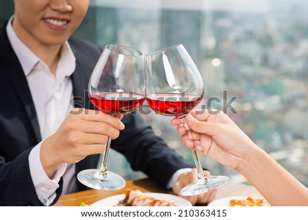 Close-up of couple clinking glasses of red wine in the restaurant