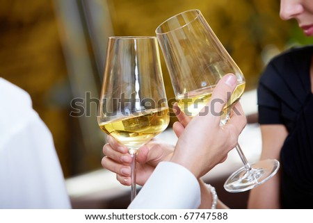 Close-up of couple hands holding champagne flutes during celebration - stock photo