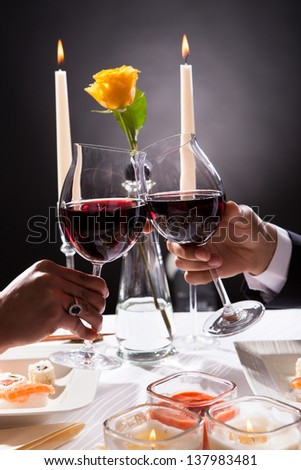 Close -up Of Couple Hands Toasting Red Wine Over Grey Background - stock photo