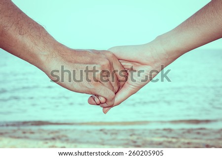 Close up of couple holding hands with sky, beach and sand background