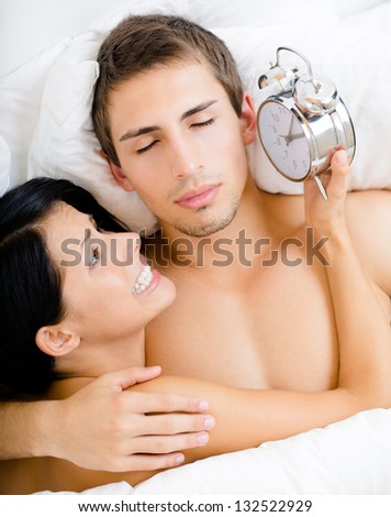 Close up of couple lying in bed. Woman holds alarm clock near the ear of man, top view - stock photo