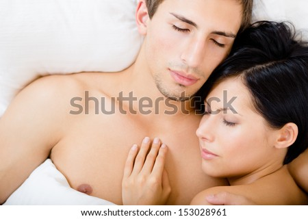 Close up of couple sleeping in bedroom, top view. Concept of love and affection - stock photo
