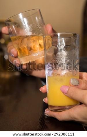 Close up of couple toasting whiskey glasses - stock photo