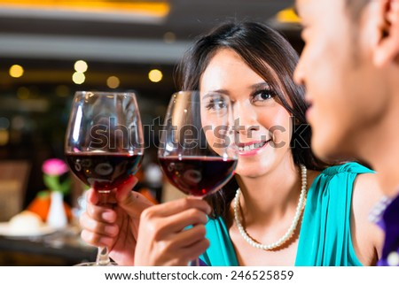 Close up of couple toasting with red wine