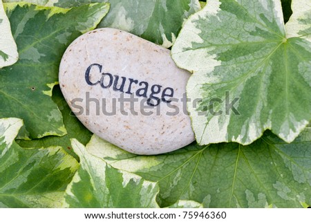 close up of 'courage' stone on ivy leaf background