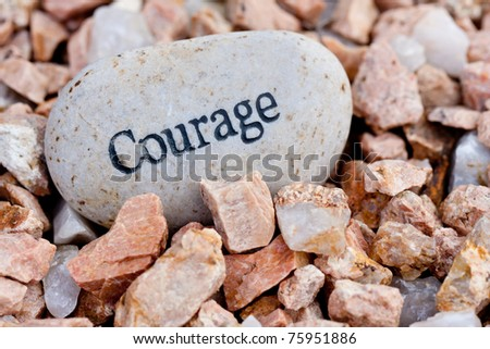 close up of 'courage' stone on textured stone background