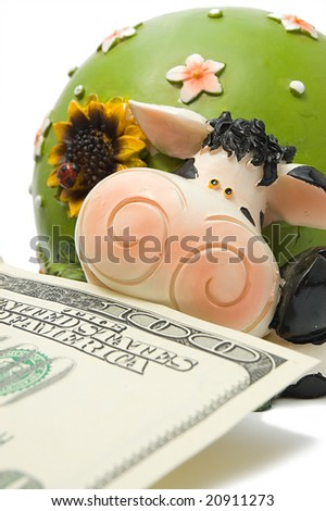 Close-up of cow-coin box with hundred dollar denomination in her mouth, symbol of 2009 - stock photo