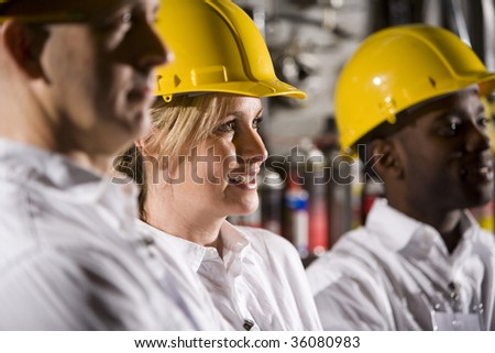 Close up of coworkers wearing hard hats - stock photo