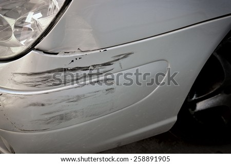 Close-up of crashed car's front area with cracks.