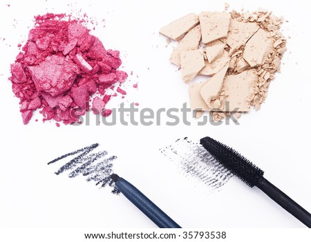 Close up of crashed cosmetics with black pencil and mascara on white background