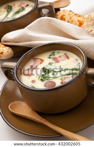 Close up of creamy Broccoli Chowder Soup with beacon, potato, and broccoli. Cheddar rosemary breadsticks. - stock photo