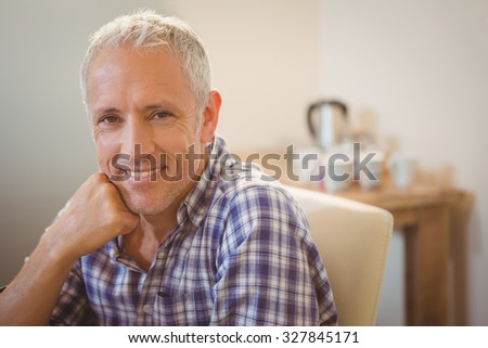 Close-up of creative businessman with hand on chin in office