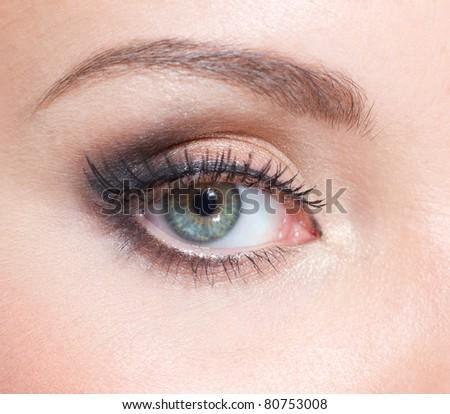 Close up of creative make up on female green eye - stock photo