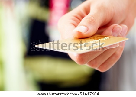 Close-up of credit card in human hand in the shop - stock photo