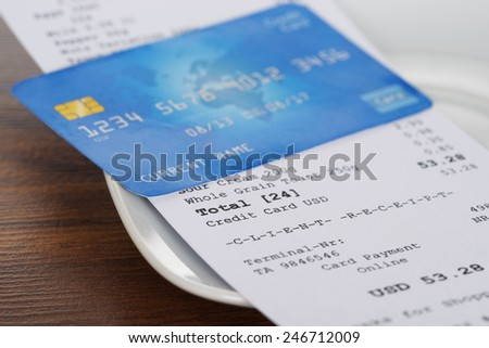 Close-up Of Credit Card On Shopping Receipt On Wooden Table - stock photo