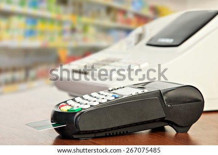 Close up of Credit Card Reader and Cash Register on background of Retail Shelves - stock photo