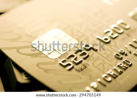 Close up of credit card with chip and numbers, golden theme - stock photo