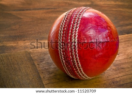 Close up of cricket ball on wooden bat - stock photo