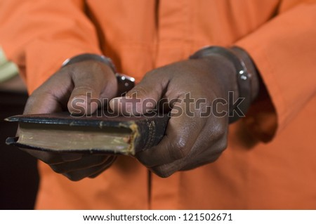 Close up of criminal's hand in handcuffs taking oath - stock photo