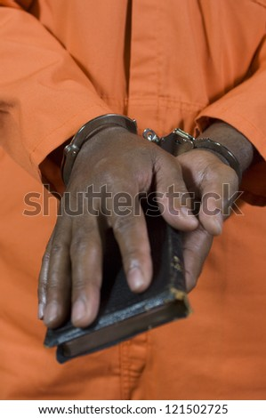 Close up of criminal's hand in handcuffs taking oath in court house - stock photo