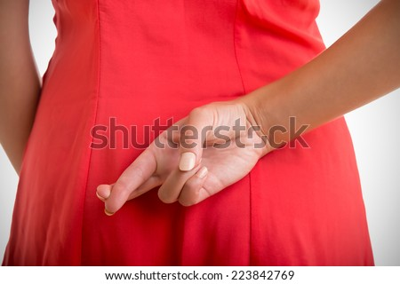 Close up of crossed fingers behind a woman's back - stock photo