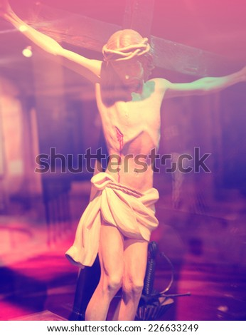 Close Up of Crucifixion Statue with Dramatic Pink Lighting - stock photo