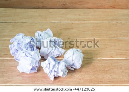 close-up of crumpled paper ball on wooden table - stock photo