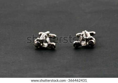 Close up of cufflinks facing each other motorbikes over black - stock photo