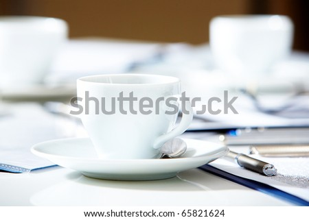 Close-up of cup of tea or coffee on the table with pen and papers near by - stock photo