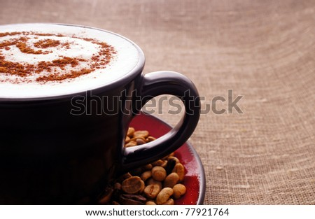 close up of cup with hot cuppuccino and cinnamon - stock photo