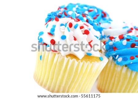 Close up of cupcakes decorated in patriotic red, white and blue.  On white with copy space.