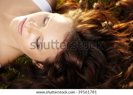 Close up of curly hair and face of beautiful girl lying on a lawn - stock photo